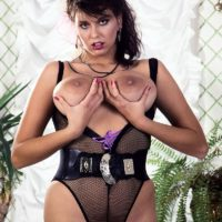 Accomplished MILF adult vid star Jeannine Oldfield tongues the erect nips of her huge tits in semitransparent lingerie