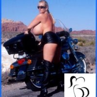 Experienced model Kayla Kleevage puts her enormous boobs on exhibit in leather by a motorcycle