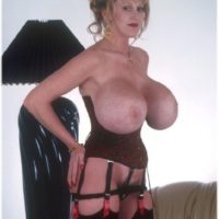 Senior solo model Kayla Kleevage shows her humungous fake tits in a waistline cincher