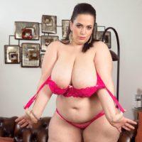 Fat stunner Mia Bombshell disrobing down to pink bra and panty set on sofa