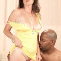 Old woman Gillian Sloan flashes her clean-shaven snatch on the lap of youthful ebony boy