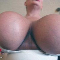 Platinum yellow-haired gal Claudia Marie holds her big boobies while sucking on a nip