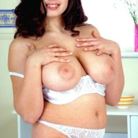 Plump black-haired pornographic starlet Kerry Marie setting her enormous MILF boobies free of lingerie