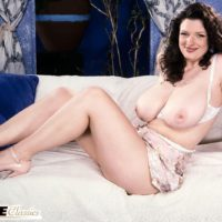 Stunner Olga sports curly hair while setting her amazing breasts free on top of her bed