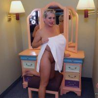 Solo model Claudia Marie showcases her huge breasts while on a bed and in a bath