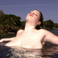 Solo model Desirae plays with her big tits while spending time in the water