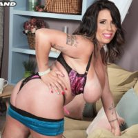 Tattooed dark-haired MILF Amaya May extracts her massive boobs from her bra in a miniskirt