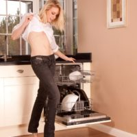 Tempting senior lady revealing her beguiling butt and furry cooch while peeling off denim jeans in a kitchen