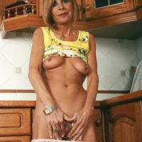 Thin senior gal revealing saggy boobies and bare buns in the kitchen for a nude spread
