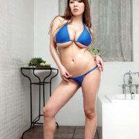 Asian babe Hitomi sports long crimson hair while loosing her big breasts from a swimsuit