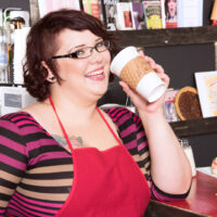 Ginger-haired BBW Kitty McPherson sports short hair and glasses while disrobing in an eatery