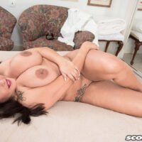 Tatted dark haired solo female Cat Bangles unveils her monster-sized tits during upskirt play