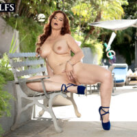 Huge-chested elder redhead Syren De Mer out on a poolside patio in stilettos