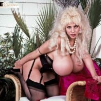 Notorious XXX actress Lulu Devine whips out her large breasts in see thru pantyhose and garters