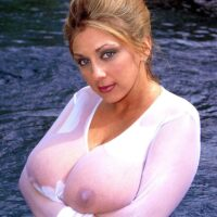 Solo model Autumn Jade demonstrates her immense boobs in a body of water while wearing a see thru outfit