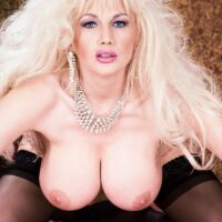 Natural blond Jay Sweet displays her big tits in a black g-string and hosiery