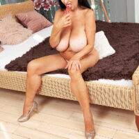 Busty dark-haired granny Mona Marley looses her suntanned assets before masturbating