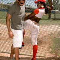 Black girl Kali Desires letting her large tush free from a baseball uniform while outdoors