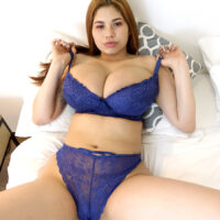 Red-haired Latina chcik Lucy Rodriguez plays with her monster-sized breasts while getting au naturel on a bed