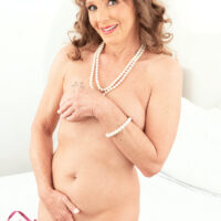 Middle-aged lady Cyndi Sinclair finger stretches her cunny after getting buck naked