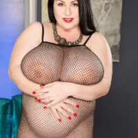 Pregnant dark haired chick Natalie Fiore pulls her massive tits act of a fishnet bodystocking