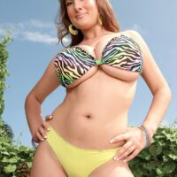 Solo model Valory Irene poses in an outdoor garden setting while wearing a brassiere and g-string