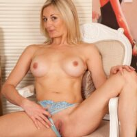 Elderly platinum-blonde model vaunting gigantic boobs and trimmed gash after shedding a sundress