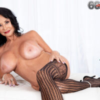 Granny X-rated film star Rita Daniels unsheathes her gigantic breasts before sucking and milking a fake penis