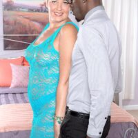 Blonde grannie Tracy Licks shows her bare titties to an ebony guy in a revealing dress