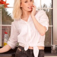 Mature platinum-blonde doll removes jeans in a kitchen to toy her fur covered coochie in barefeet