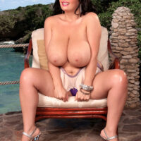 Immense titted brunette Arianna Sinn plays with her hard nipples after getting naked on a patio