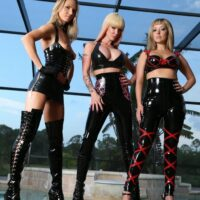 Ash-blonde dommes Alexia, Tyler and Alina model spandex wear in front of a swimming pool