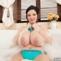Brunette MILF Joana Bliss letting jer large all-natural breasts loose from a bathing suit in a bathtub